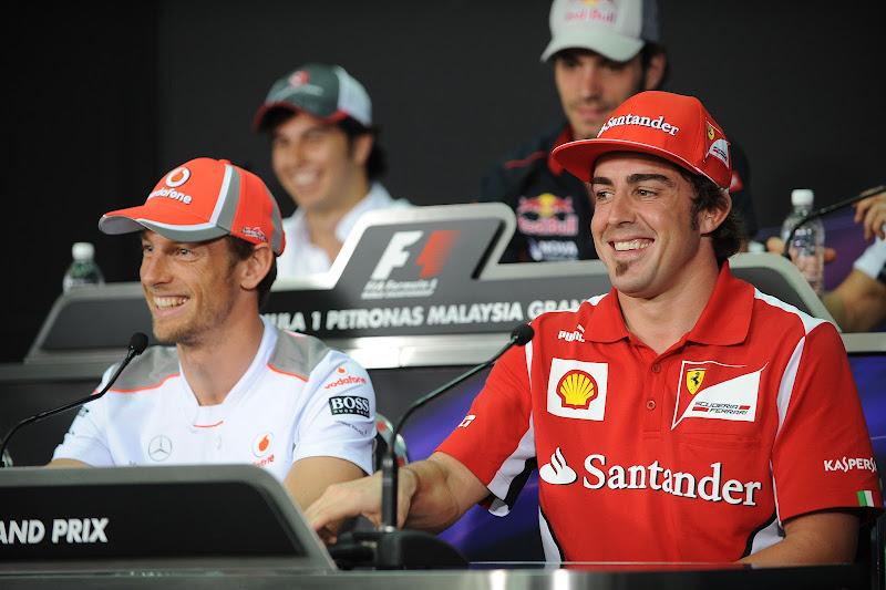улыбающиеся Дженсон Баттон и Фернандо Алонсо на пресс-конференции в четверг на Гран-при Малайзии 2012
