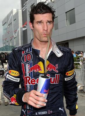 Марк Уэббер идет по паддоку и пьет из банки Red Bull