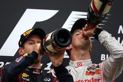 Себастьян Феттель и Дженсон Баттон пьют шампанское на подиуме Хунгароринга на Гран-при Венгрии 2011