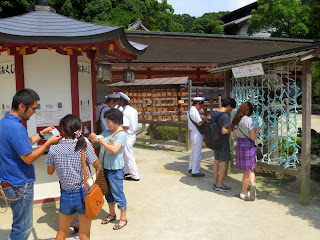 People checking their o-mikuji at the Dazaifu shrine