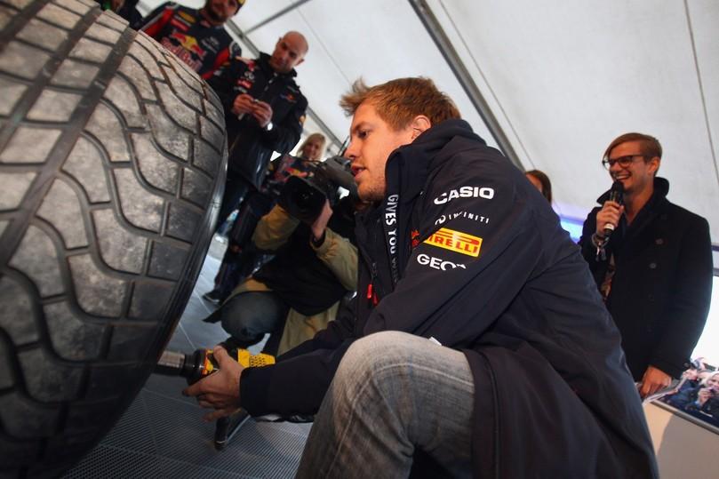 Себастьян Феттель закручивает колесо гайковертом на своем Red Bull в Хеппенхайме 20 октября 2011