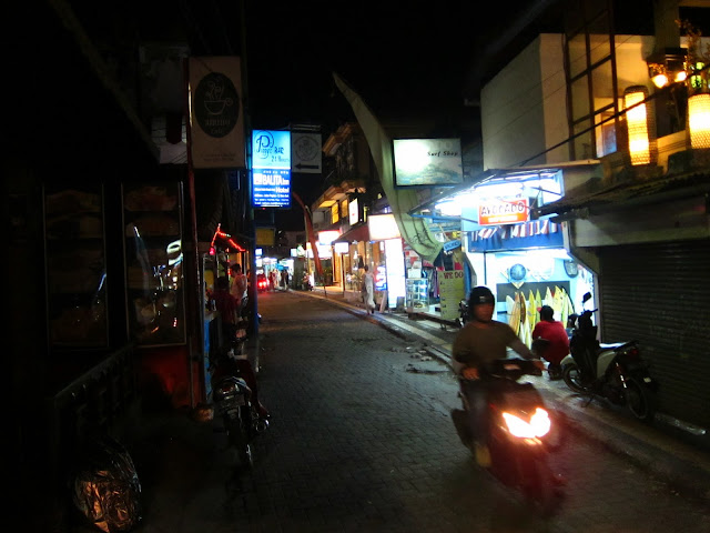 Look out! Motorbikes dodge pedestrians on Kuta's small and congested back alleys.