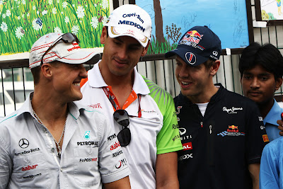улыбающиеся Михаэль Шумахер Адриан Сутиль и Себастьян Феттель на Гран-при Индии 2011