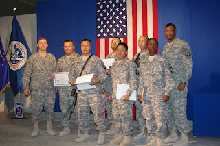 Six new citizens stand with their brigade commander and Command Sgt. Maj.