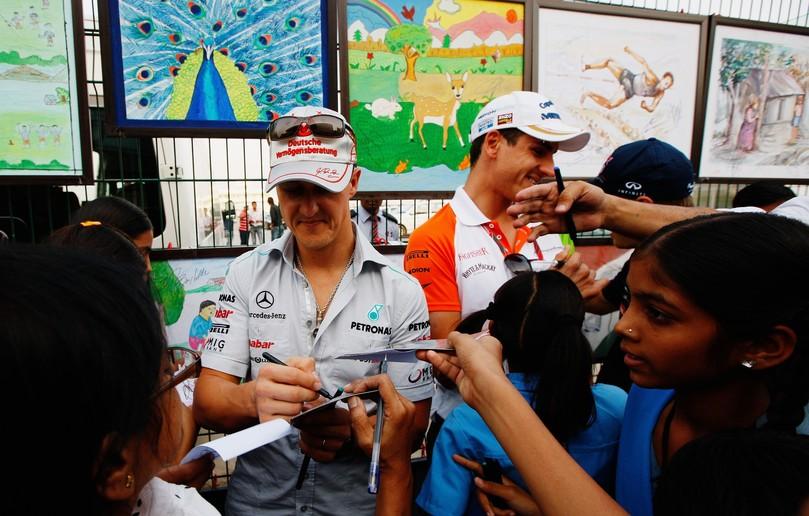Михаэль Шумахер и Адриан Сутиль раздают автографы индийским детям на Гран-при Индии 2011