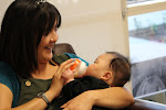 LePort Preschool Huntington Beach -  - Teacher feeding infant at Montessori childcare