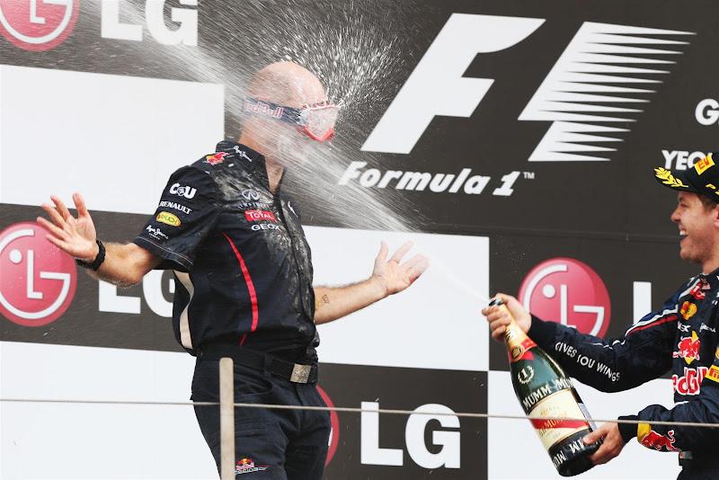Эдриан Ньюи в очках и Себастьян Феттель с шампанским на подиуме Йонама на Гран-при Кореи 2012