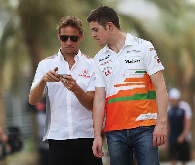 Дженсон Баттон с телефоном и Пол ди Реста идут по паддоку Сахира на Гран-при Бахрейна 2013
