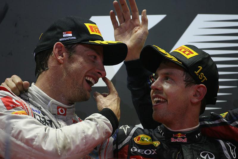 Дженсон Баттон показывает палец Себастьяну Феттелю на подиуме Гран-при Сингапура 2011