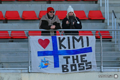 болельщики Кими Райкконена на трибунах с баннером на предсезонных тестах в Барселоне - март 2013
