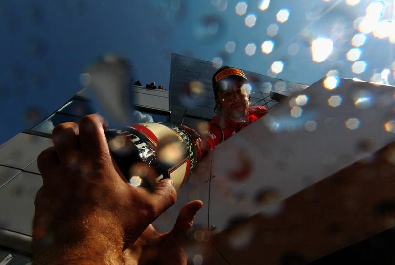 Фернандо Алонсо кидает бутылку шампанского механикам с подиума Сильверстоуна после победы на Гран-при Великобритании 2011