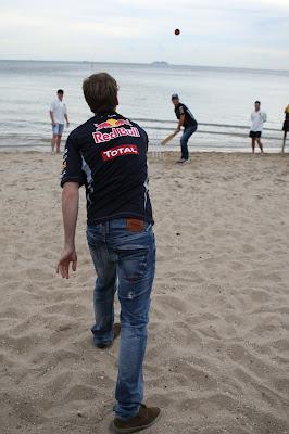 Себастьян Феттель кидает мяч Марку Уэбберу на пляже в Мельбурне перед Гран-при Австралии 2012