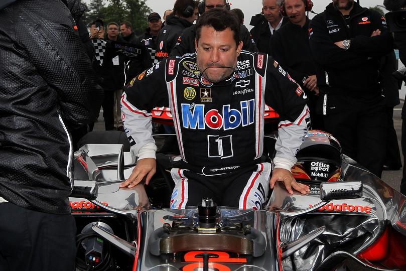 Тони Стюарт пытается залезть в болид McLaren Льюиса Хэмилтона в Уоткинс-Глене на Mobil 1 Car Swap 2011