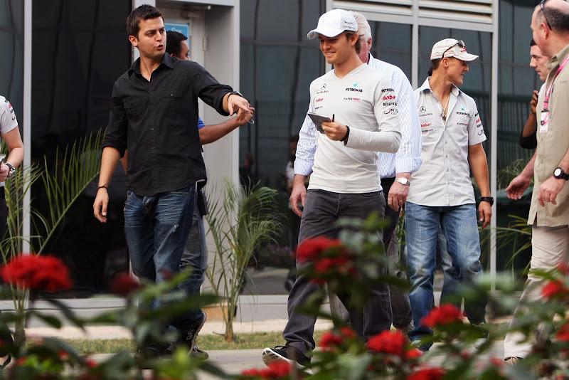Нико Росберг и Михаэль Шумахер идут по паддоку на Гран-при Индии 2011