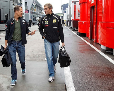 Михаэль Шумахер и Виталий Петров гуляют по паддоку с сумками на Гран-при Венгрии 2011