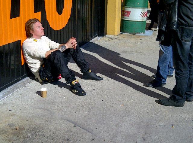 Кими Райкконен сидит у гаража со стаканчиком кофе на тестах в Валенсии 24 января 2012