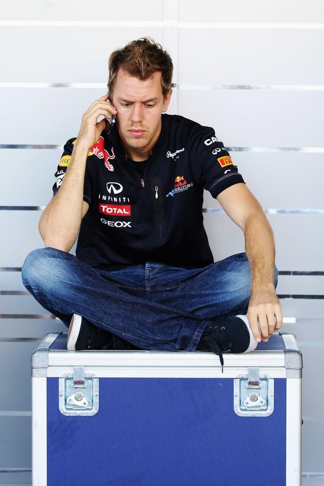 Себастьян Феттель сидит на ящике и разговаривает по телефону на Гран-при Японии 2011