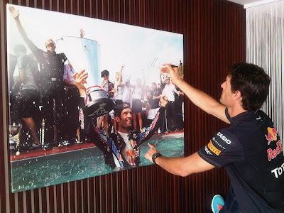 Марк Уэббер подписывает постер со своей фотографией на Гран-при Монако 2011