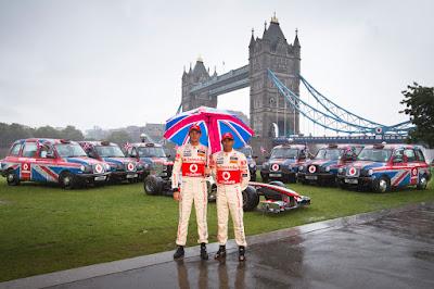 Дженсон Баттон и Льюис Хэмилтон под зонтиком в Лондоне на фоне Тауэрского моста перед Гран-при Великобритании 2011 на мероприятии Vodafone