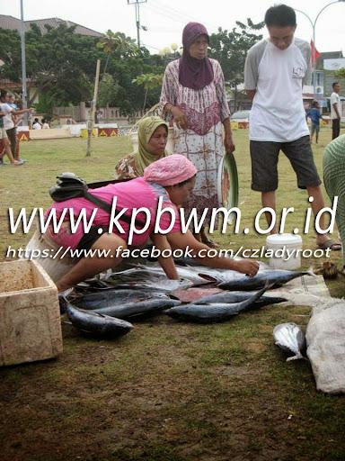 ibu yang sedang menjual ikan di depan taman kota majene