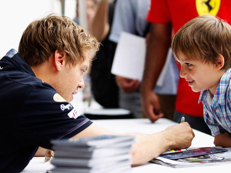 Себастьян Феттель дает автограф мальчику на Гран-при Канады 2011