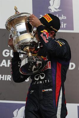 Себастьян Феттель целует кубок на подиуме Гран-при Бахрейна 2013