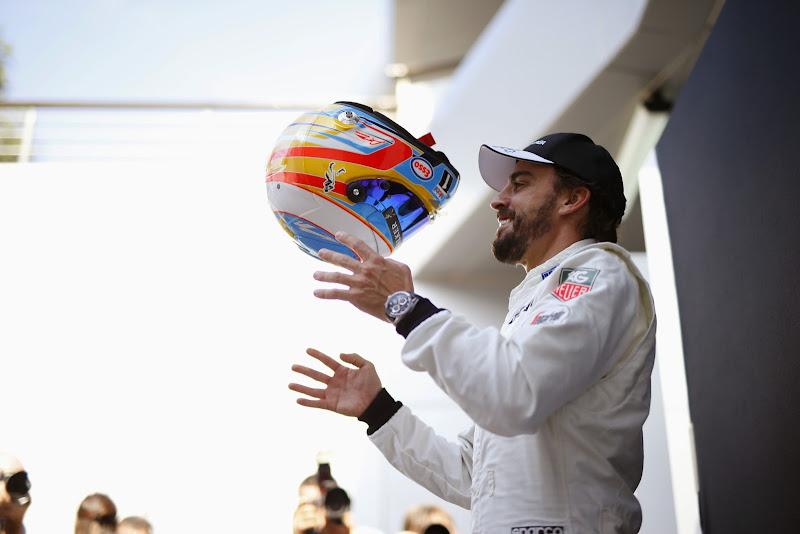 Фернандо Алонсо подбрасывает шлем на Гран-при Малайзии 2015