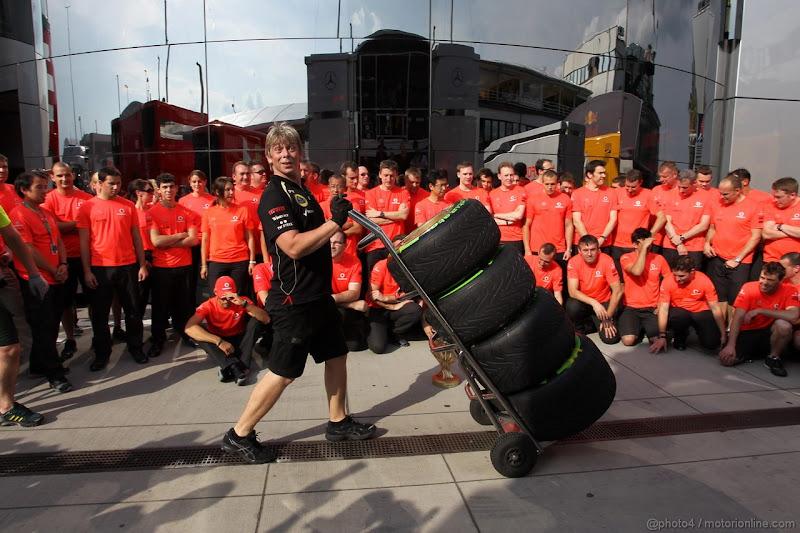 механик Lotus провозит резину Pirelli перед групповой фотографией McLaren на Гран-при Венгрии 2012
