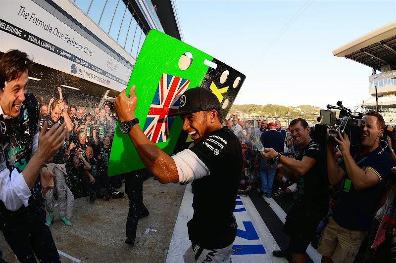 Льюис Хэмилтон спасается от шампанского на праздновании победы в кубке конструкторов на Гран-при России 2014