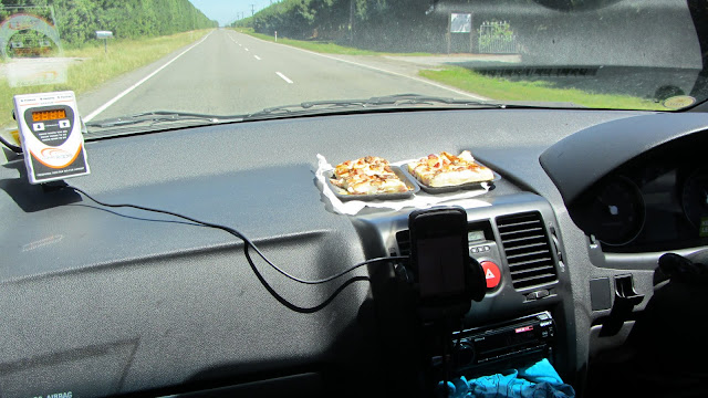 Toasting our lunchtime frittatas on the car's black dashboard.