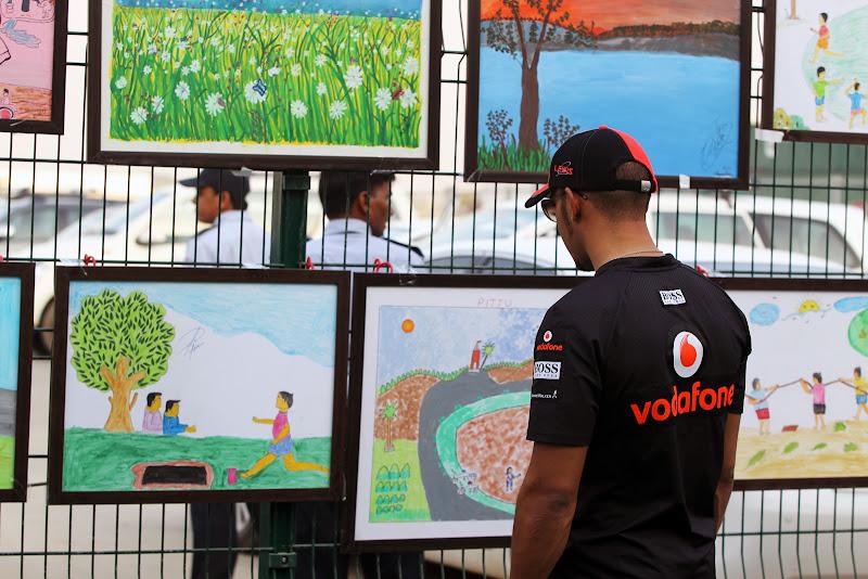 Льюис Хэмилтон разглядывает рисунки индийских школьников на Гран-при Индии 2011