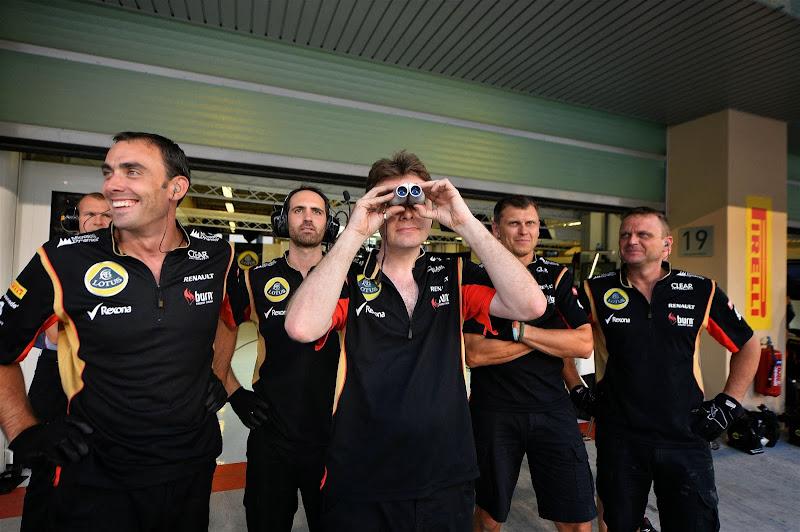 механики Lotus смотрят в бинокль на Гран-при Абу-Даби 2013