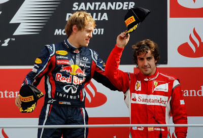 Себастьян Феттель и Фернандо Алонсо с кепкой в руках на подиуме Монцы на Гран-при Италии 2011