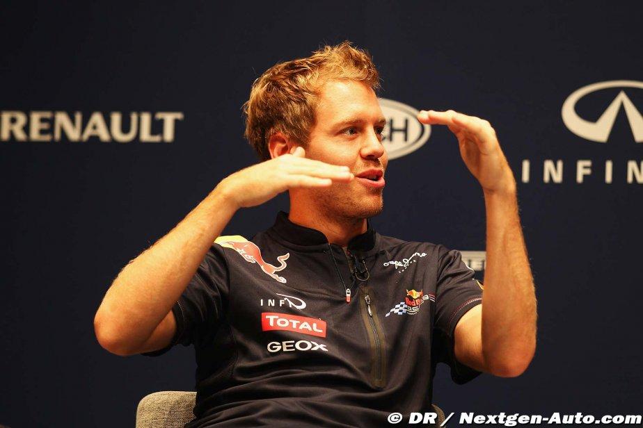 Себастьян Феттель показывает что-то руками на пресс-конференции Red Bull в Йокогаме