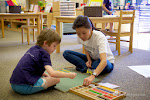 Teachers in Montessori elementary often work with one student or a small group of students. Here, a child receives an individual lesson with the Box of Sticks. This materials helps children learn about the property of lines (parallel, convergent, divergent) and of angles (acute, obtuse, right).
