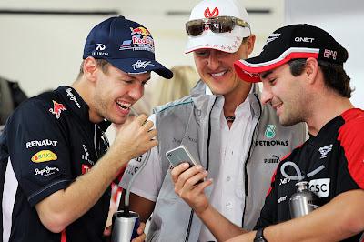 Тимо Глок показывает что-то смешное на телефоне Себастьяну Феттелю и Михаэлю Шумахеру на Гран-при Индии 2012