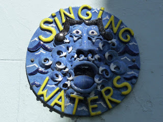 """Singing Waters"" plaque on building"