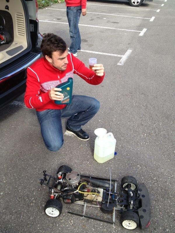 Фернандо Алонсо заправляет радиоуправляемую машинку маслом и топливом 8 марта 2013