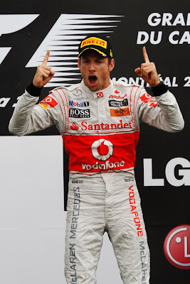 Джон Баттон с поднятыми пальцами и открытым ртом на подиуме Гран-при Канады 2011
