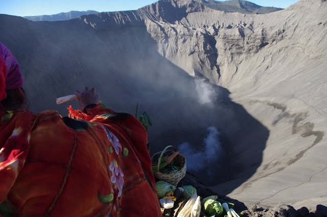 Perched atop the rim and looking into the crater, a Tenggerese woman makes offerings to the volcano.