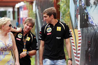 улыбающиеся Виталий Петров и Оксана Косаченко идут по паддоку Сингапура на Гран-при Сингапура 2011