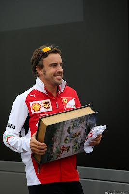 Фернандо Алонсо несет здоровенную книгу по паддоку Монцы на Гран-при Италии 2014