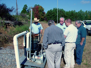 Soil Vapor Extraction System custom-built by AEM. AEM's Field Manager Eric Benton (second from right with back to camera) discusses operational issues with site owners and County maintenance crew.