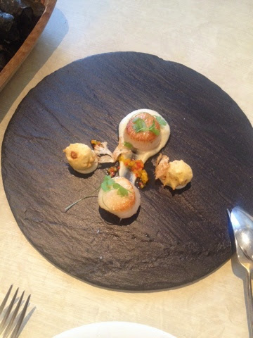 Scallops with cauliflower served on a round slate tray