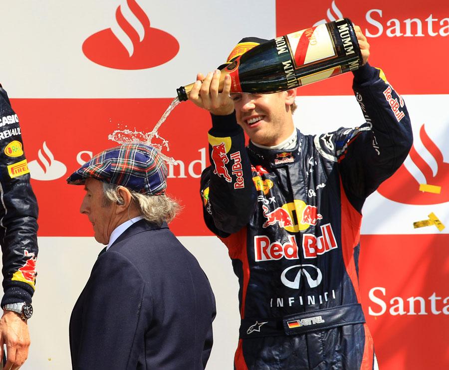 Себастьян Феттель поливает Джеки Стюарта шампанским на подиуме Гран-при Великобритании 2012