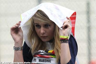 девушка маршал спасается от дождя на пит-лейне Гран-при Бельгии 2011 в Спа-Франкошам