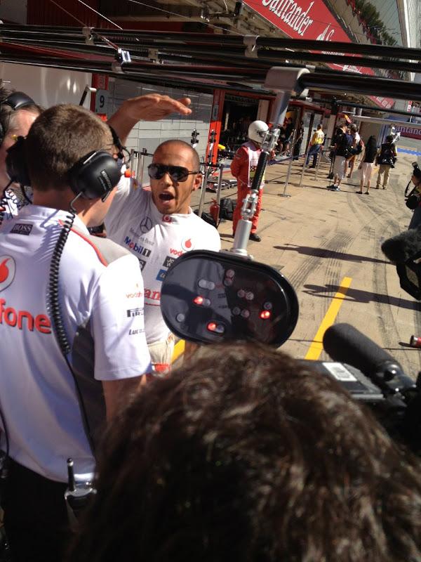 Льюис Хэмилтон показывает что-то своим механикам в пятницу на Гран-при Испании 2012