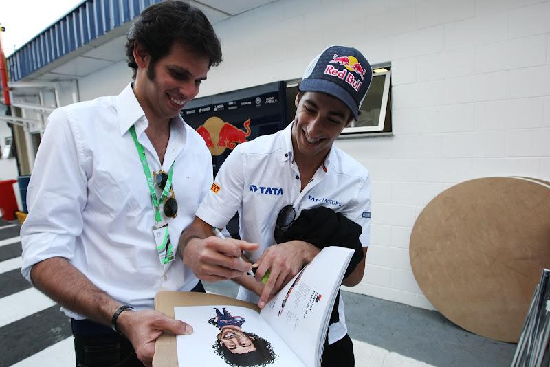 Даниэль Риккардо ставит автограф на своей карикатуре из книжки VROOOM на Гран-при Бразилии 2011