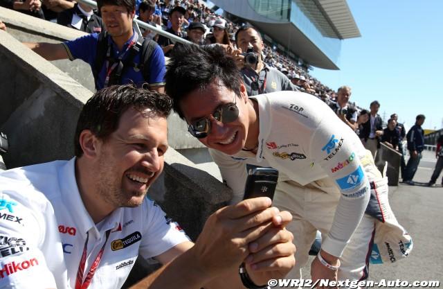 механик показывает что-то смешное на телефоне Камуи Кобаяши на Гран-при Японии 2011