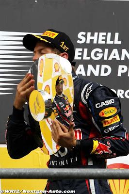 Себастьян Феттель целует трофей в отражении которого Марк Уэббер на подиуме Гран-при Бельгии 2011